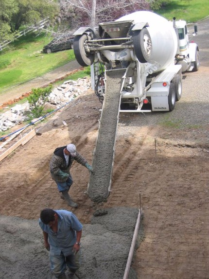 Construction crew pouring a concrete driveway from a ready mix concrete truck in Carmichael California